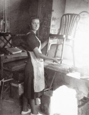 Mujer puliendo a mano una silla para un cliente
